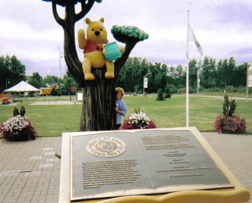 Deb Hoffmann with the Pooh statue in Pooh Park in White River Ontario Canada.